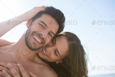 Smiling couple embracing at beach