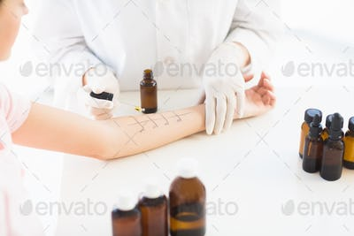 Midsection of doctor dropping medicine on patient hand