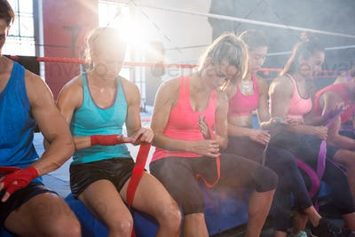 Back lit athletes sitting on boxing ring while wrapping bandages