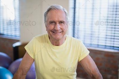 Portrait of smiling senior male patient against window
