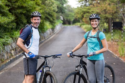 Athletic couple standing with mountain bike on the open road