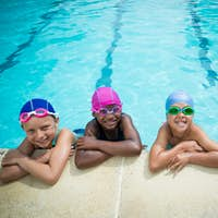 Little swimmers leaning at poolside