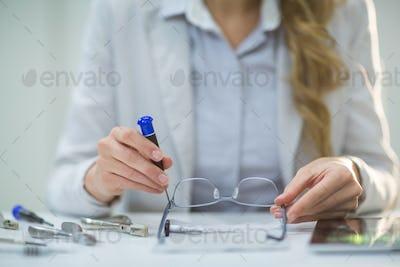 Female optometrist preparing glass frame