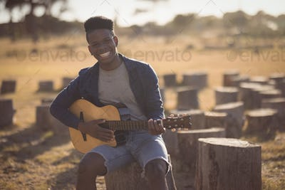 Portrait of smiling young man playing guitar while sitting in forest