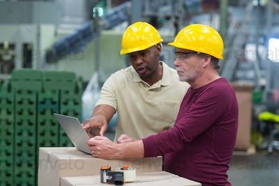 Factory workers discussing while working on laptop in drinks production plant