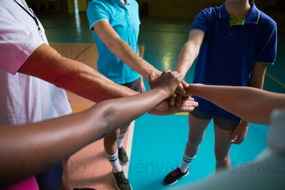 Volleyball players and coach forming hand stack