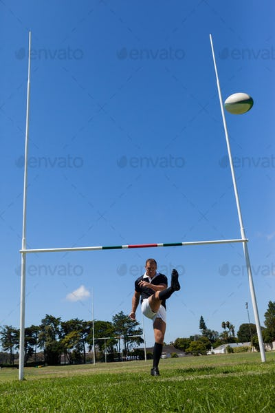Rugby player kicking ball through goal post