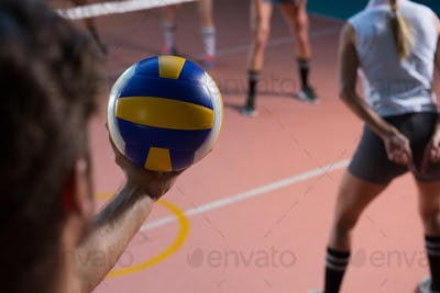 Cropped hand of player holding volleyball by female teammate