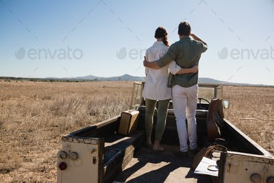 Rear view full length of couple on off road vehicle at landscape