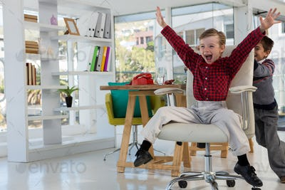 Boy as business executives pushing his colleague on chair