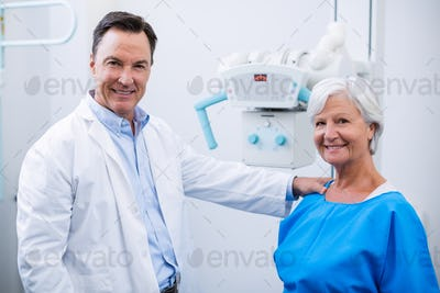 Portrait of smiling doctor and senior woman during medical check-up