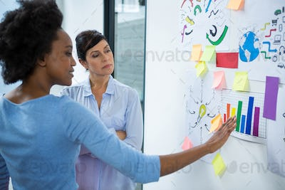 Female graphic designer pointing to the sticky notes on the glass in creative office