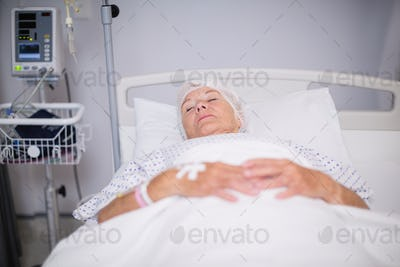 Senior woman patient wearing oxygen mask lying on bed