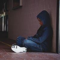 Full length of sad boy sitting wall in corridor