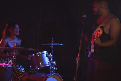 Man playing guitar with female drummer
