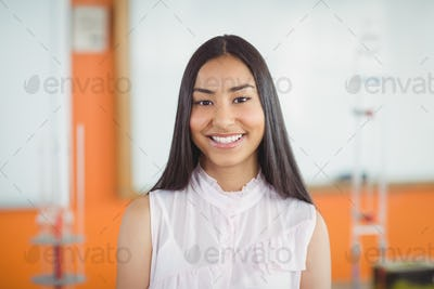 Portrait of smiling schoolgirl in classroom