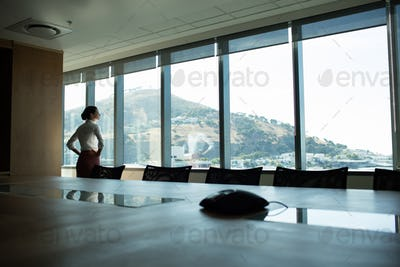 Businesswoman looking through window in conference room