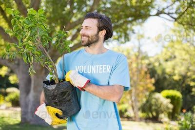 A volunteer man holding plant