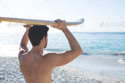 Rear view of shirtless man carrying surfboard at beach