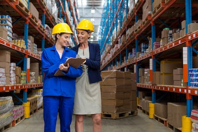 Warehouse manager and worker discussing with clipboard