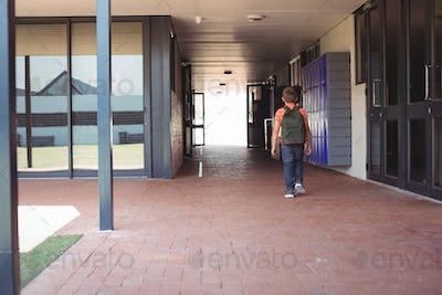 Full length of boy with backpack walking in corridor