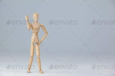 Wooden figurine standing and showing his fist