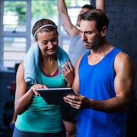 Athletes looking in tablet computer at gym