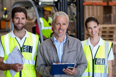 Portrait of warehouse manager and workers standing together