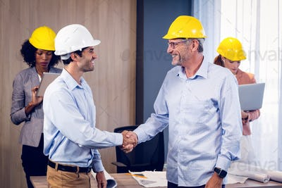 Two architects shaking hands in office