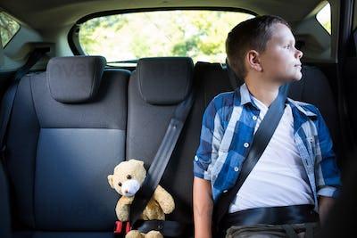 Teenage boy sitting with teddy bear in the car
