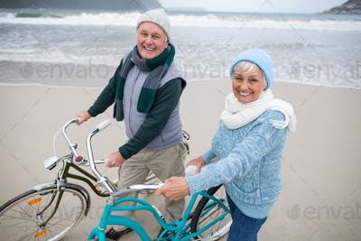Portrait of senior couple standing with bicycles on the beach
