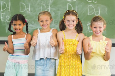 Smiling kids showing thumbs up in classroom