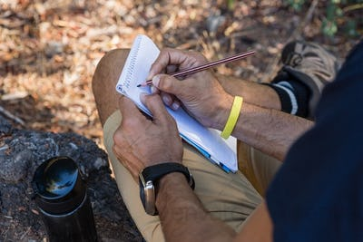 Man writing on notepad while resting on tree trunk