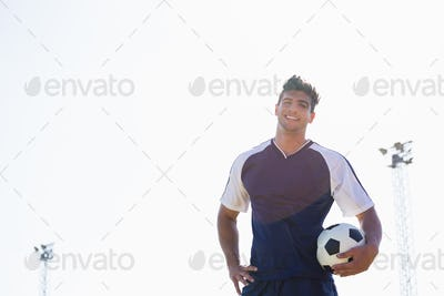 Happy football player standing with a ball