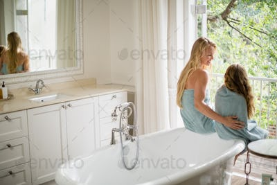 Mother and daughter interacting with each other in bathroom