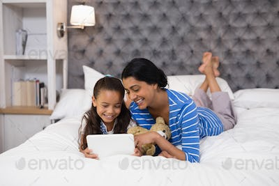 Mother and daughter using digital tablet while lying on bed at home