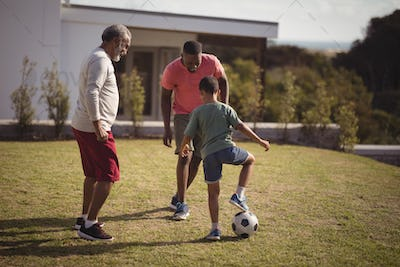 Boy playing football with his father and grandson