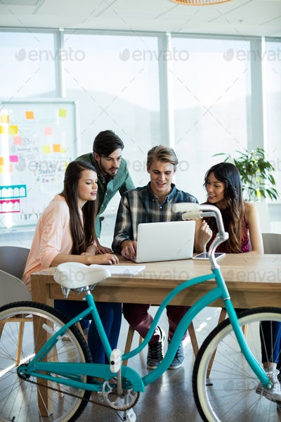 Smiling creative business team discussing over laptop