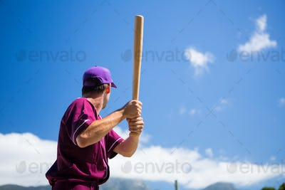 Low angle view of baseball player holding bat against blue sky