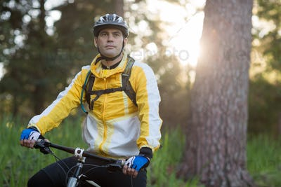 Male biker with mountain bike in forest