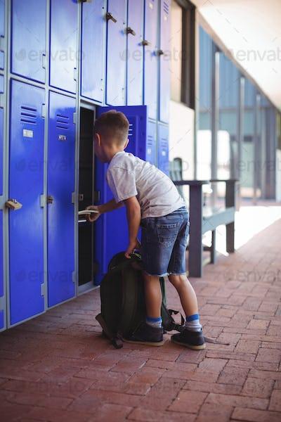 Full elngth of boy taking books from locker