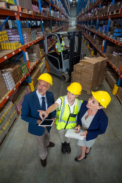 Warehouse manager interacting with client and female worker