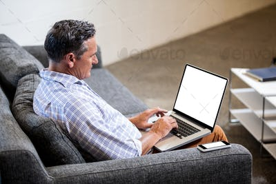 Profile view of businessman working with his laptop