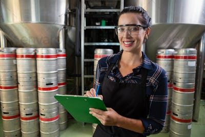 Portrait of smiling worker holding clipboard by storage tanks