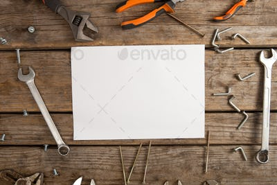 Worktools and blank paper on wooden plank