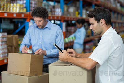 Two warehouse workers working together