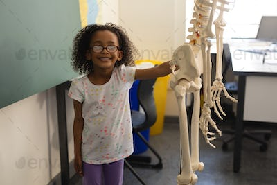 Front view of little happy black schoolgirl holding human skeleton model and looking at camera in cl