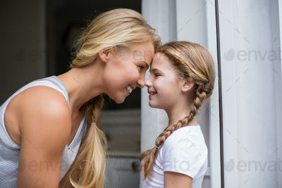 Smiling mother and daughter looking face to face