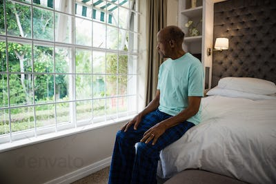 Thoughtful senior man sitting by window in bedroom