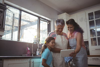 Happy family using digital tablet in kitchen